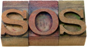 call for help - SOS word in vintage wooden letterpress printing blocks, isolated on white